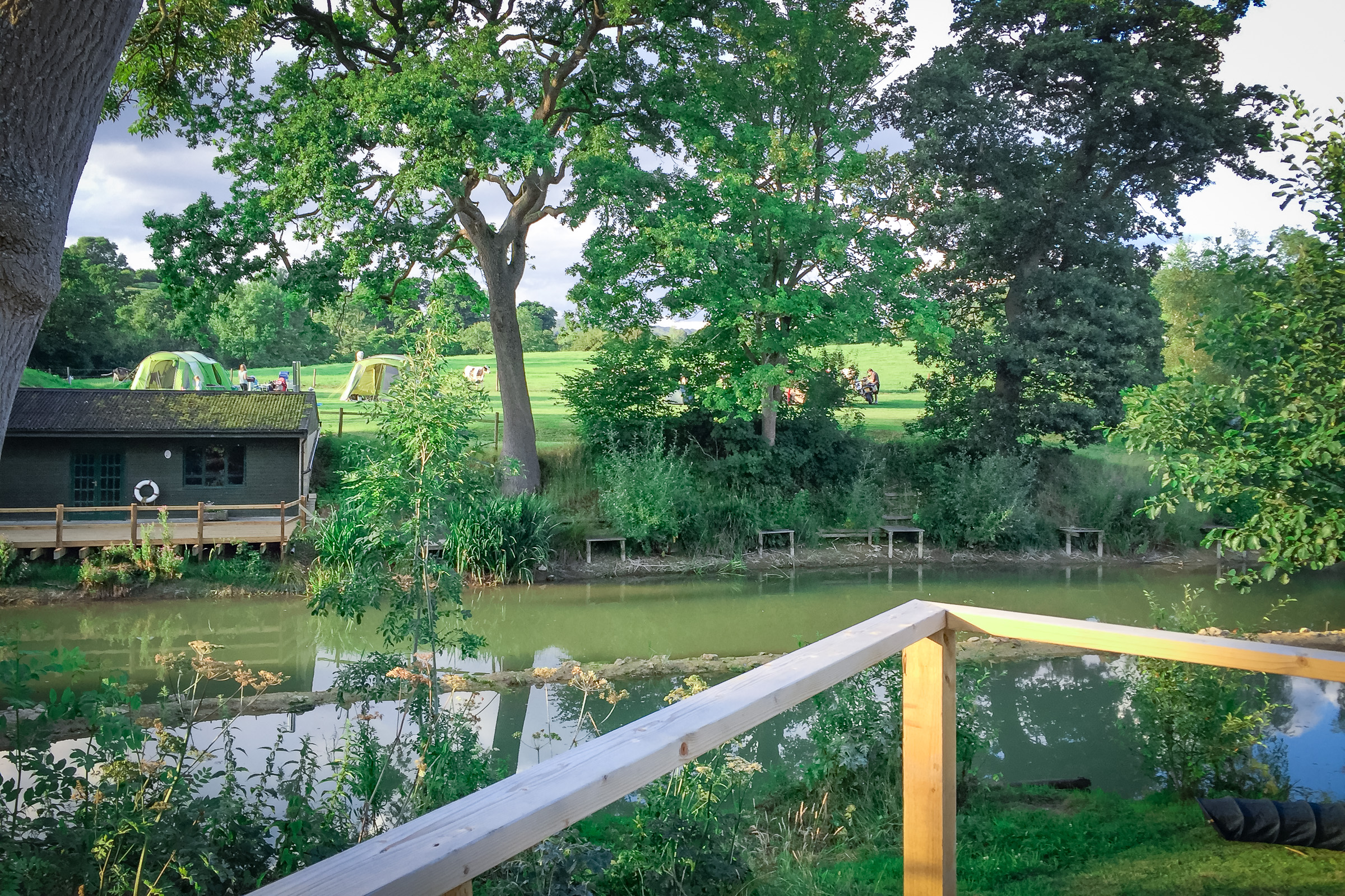 Painswick Glamping – Mill Pool Pod view of lake and tent sites